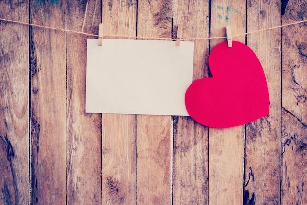 Cuore rosso appeso e carta su clothesline e corda con sfondo in legno
