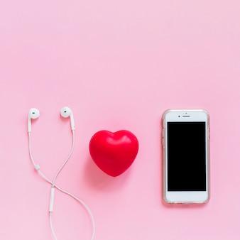 Cuore rosso; auricolare e smartphone su sfondo rosa