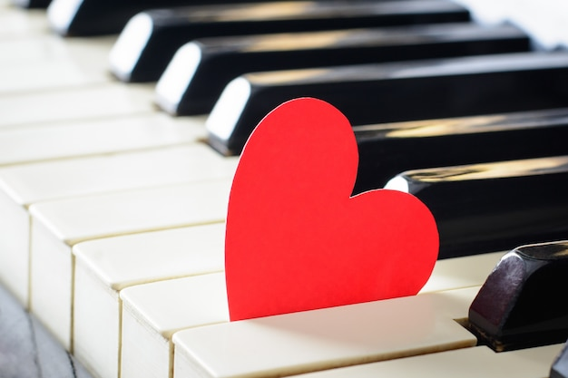 Cuore rosso brillante su una tastiera di un vecchio pianoforte. concetto di amore, san valentino