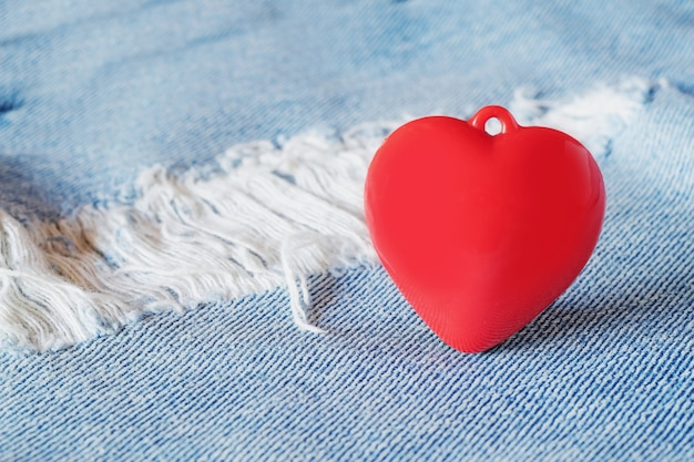 Cuore rosso che pone sopra le blue jeans vecchie e dello strappo. concetto di san valentino.