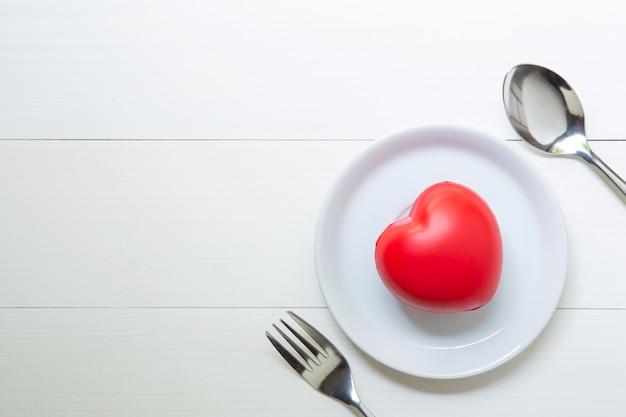Cuore rosso con amore e piatto e cucchiaio e forchetta su fondo di legno