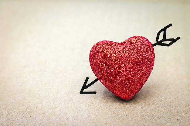 Cuore rosso con freccia di cupido su sfondo di cartone. concetto di san valentino