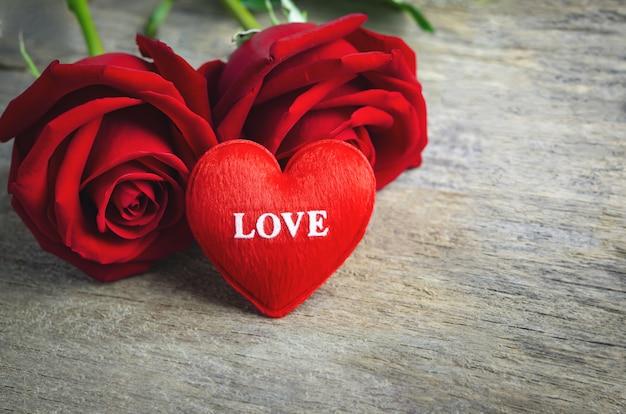 Cuore rosso con il testo di amore e fiori della rosa rossa su superficie di legno