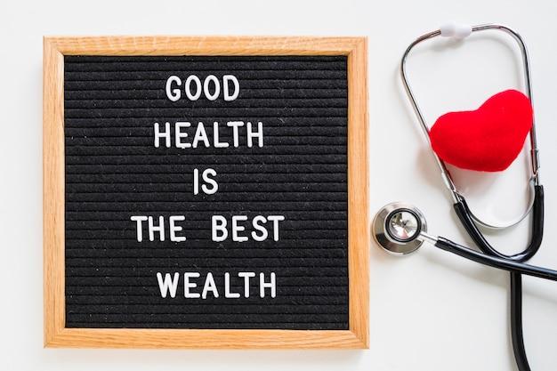 Cuore rosso con lo stetoscopio e la bacheca con il messaggio di buona salute su fondo bianco