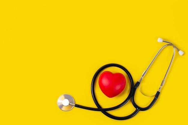 Cuore rosso con lo stetoscopio su colore giallo