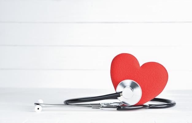 Cuore rosso con lo stetoscopio su fondo di legno bianco.