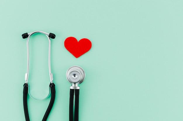 Cuore rosso con lo stetoscopio su sfondo verde menta