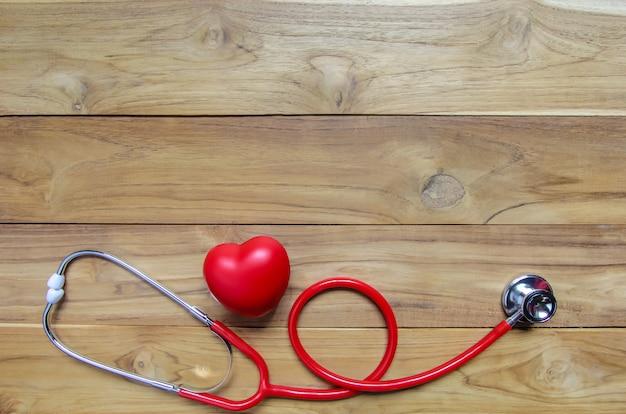 Cuore rosso con stetoscopio su fondo in legno. copyspace. cardiologia.