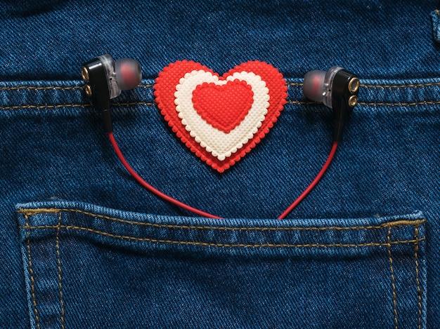 Cuore rosso e bianco con le cuffie che sporgono dalla tasca dei jeans. stile romantico in abiti alla moda.
