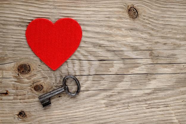 Cuore rosso e chiave d'annata su legno