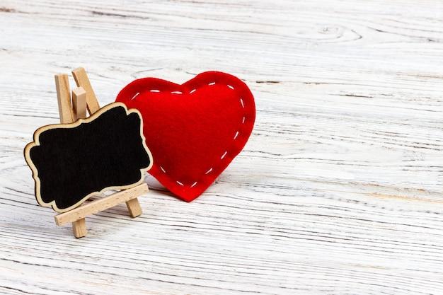 Cuore rosso e piccola lavagna. composizione di san valentino