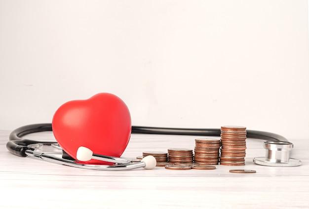 Cuore rosso e stetoscopio con monete.