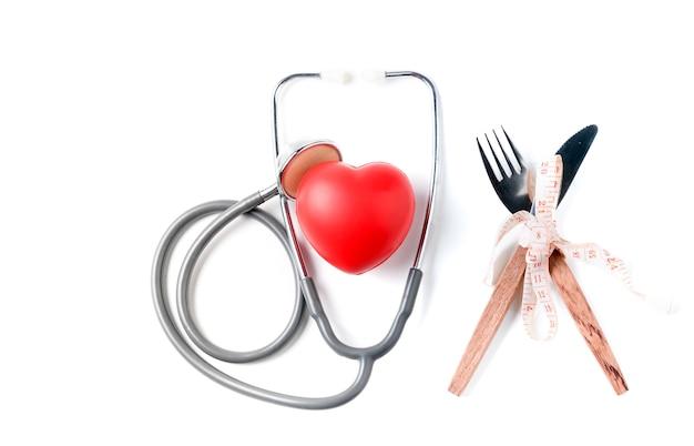Cuore rosso e stetoscopio con nastro di misurazione