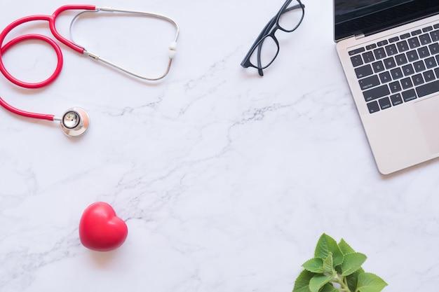 Cuore rosso e stetoscopio e laptop su sfondo di marmo bianco