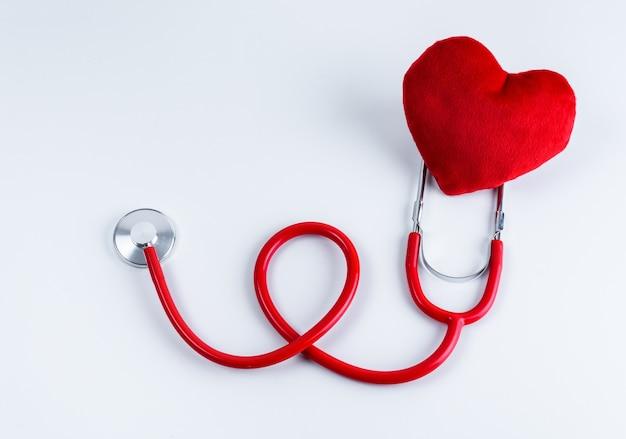 Cuore rosso e stetoscopio sul tavolo
