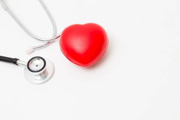 Cuore rosso e uno stetoscopio. isolato su bianco illuminazione da studio. concetto di salute e medicina