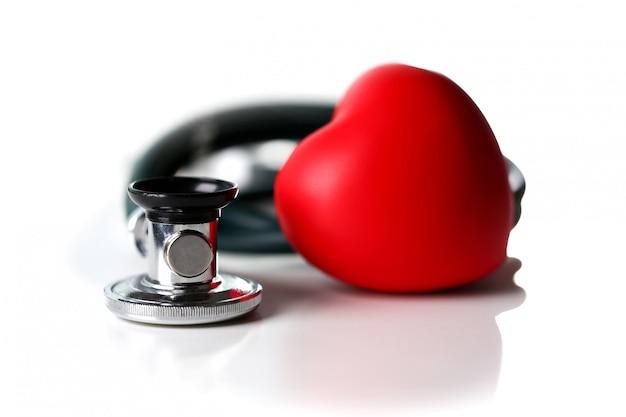Cuore rosso e uno stetoscopio su un bianco