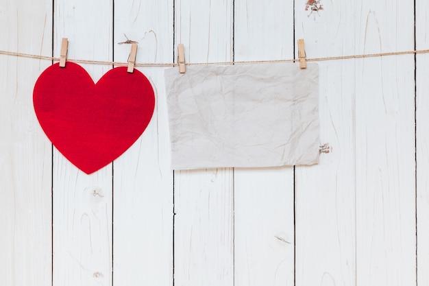 Cuore rosso e vecchio vuoto di carta appeso al clothesline su sfondo bianco di legno con spazio. san valentino.