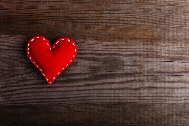 Cuore rosso fatto di feltro su un tavolo di legno