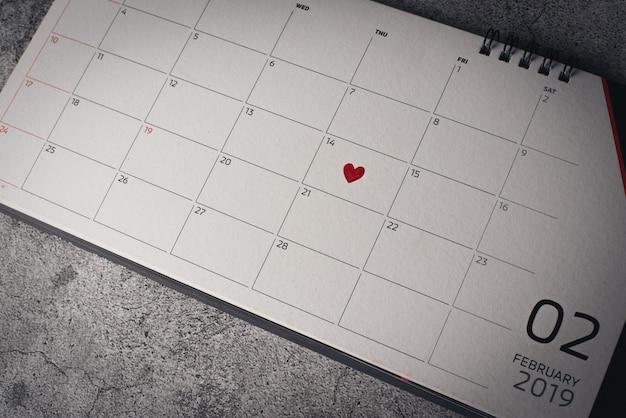 Cuore rosso in 14 febbraio sul calendario, concetto di san valentino