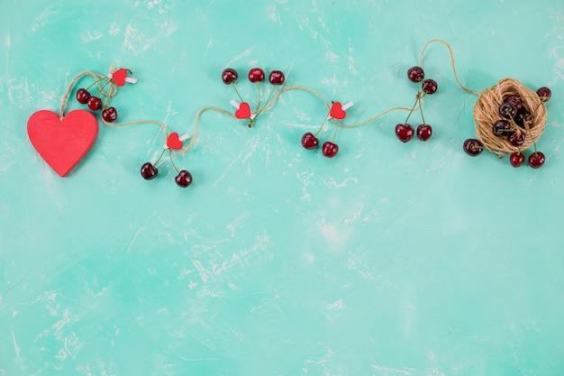 Cuore rosso in legno e ciliegie fresche dolci isolati su sfondo verde. composizione d'amore