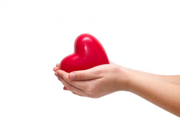 Cuore rosso in mani della donna su bianco