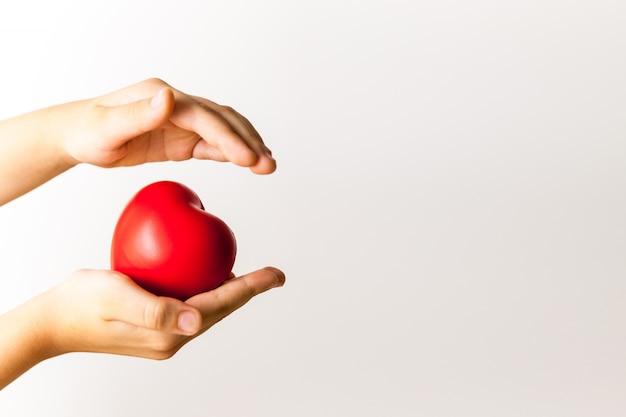Cuore rosso nelle mani del bambino su sfondo chiaro