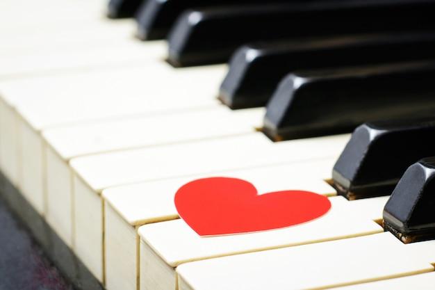 Cuore rosso sui tasti di una tastiera di un vecchio pianoforte classico