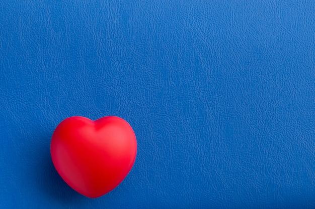 Cuore rosso sul tavolo blu