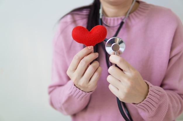 Cuore rosso sulle mani della donna con lo stetoscopio.