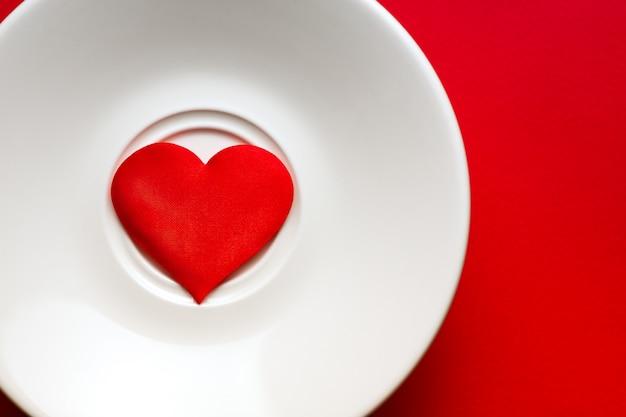 Cuore sul piatto bianco a sfondo rosso. concetto di romanticismo e amore.