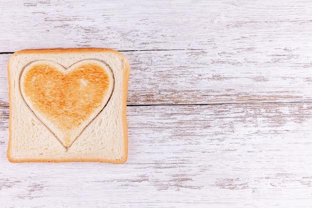 Cuore tagliato pane tostato, concetto felice di san valentino, pasto di mattina con amore