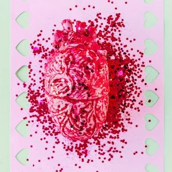 Cuore umano in ceramica rosa con lustrini su carta