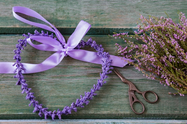 Cuore viola di fiori viola, forbici a forma di uccello e bouquet di erica