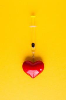 Cuore volumetrico con siringhe su uno sfondo rosa. il concetto di supportare i pazienti con malattie cardiache