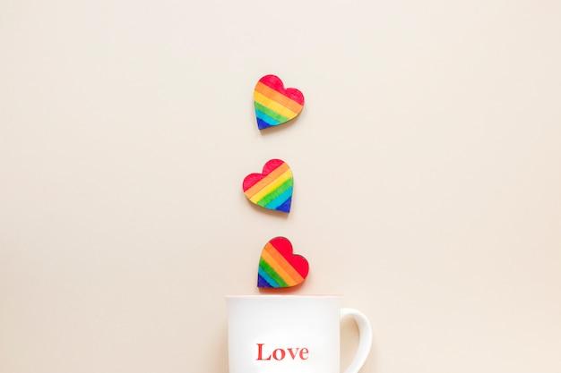 Cuori arcobaleno con tazza con iscrizione di amore