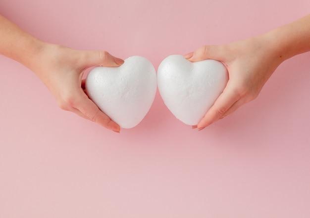 Cuori bianchi vuoti di amore in mani