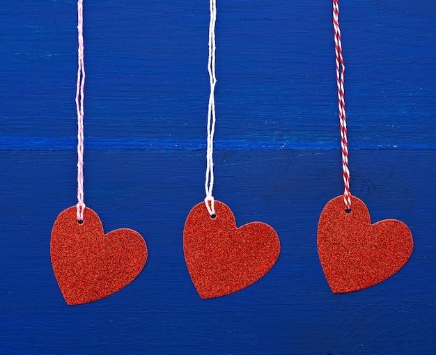 Cuori decorativi lucidi rossi di carta che appendono su una corda su un fondo di legno blu scuro