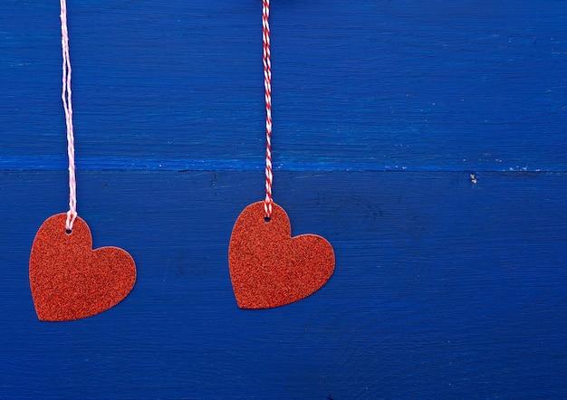 Cuori decorativi lucidi rossi di carta che appendono su una corda su un'oscurità