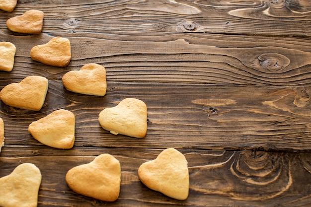 Cuori dei biscotti di cottura domestica. i biscotti a forma di cuore si trovano in diagonale sul tavolo.
