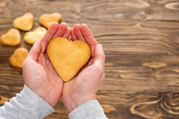 Cuori dei biscotti di cottura domestica. una persona tiene in mano un biscotto a forma di cuore.