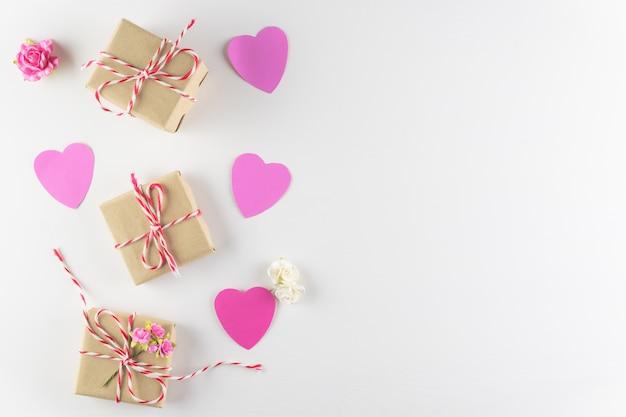 Cuori di amore rosa fatti a mano e contenitore di regalo isolato su fondo di legno bianco
