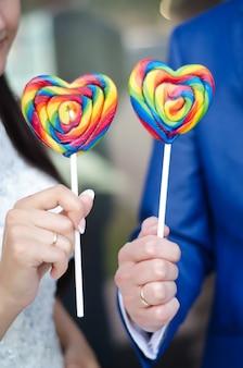 Cuori di caramelle dolci su bastoni nelle mani