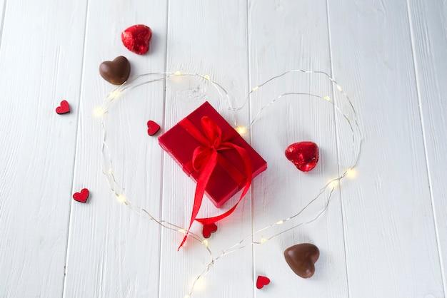 Cuori di caramelle e scatola regalo sul bordo di legno
