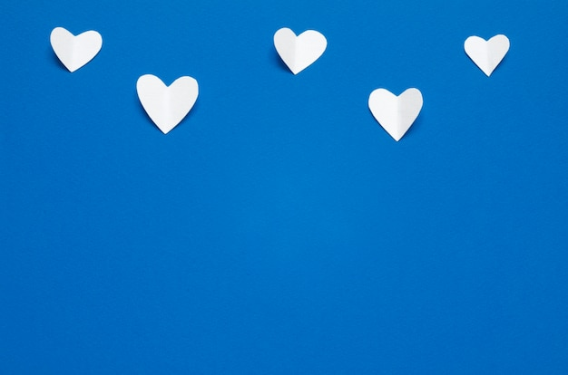 Cuori di carta bianca su sfondo blu, vista dall'alto. colore dell'anno 2020 blu classico.