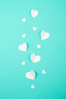 Cuori di carta bianca su sfondo turchese. sainte valentine, festa della mamma, biglietti d'auguri di compleanno, invito, celebrazione concetto