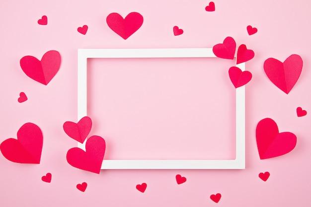 Cuori di carta e cornice bianca su sfondo rosa pastello.