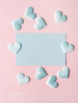 Cuori di carta pastello verde su texture rosa