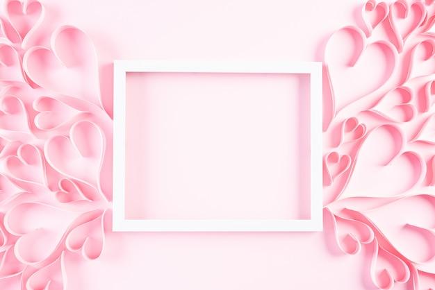 Cuori di carta rosa con cornice bianca su sfondo di carta rosa