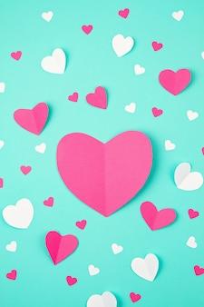 Cuori di carta rosa su sfondo turchese. sainte valentine, festa della mamma, biglietti d'auguri di compleanno, invito, celebrazione concetto